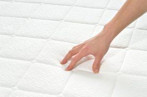 Hand auf Matratzenauflage